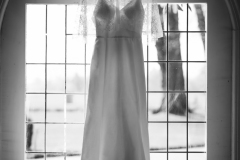 Wedding dress hanging in window of Orangery at Rothamsted Manor Harpenden, Hertfordshire